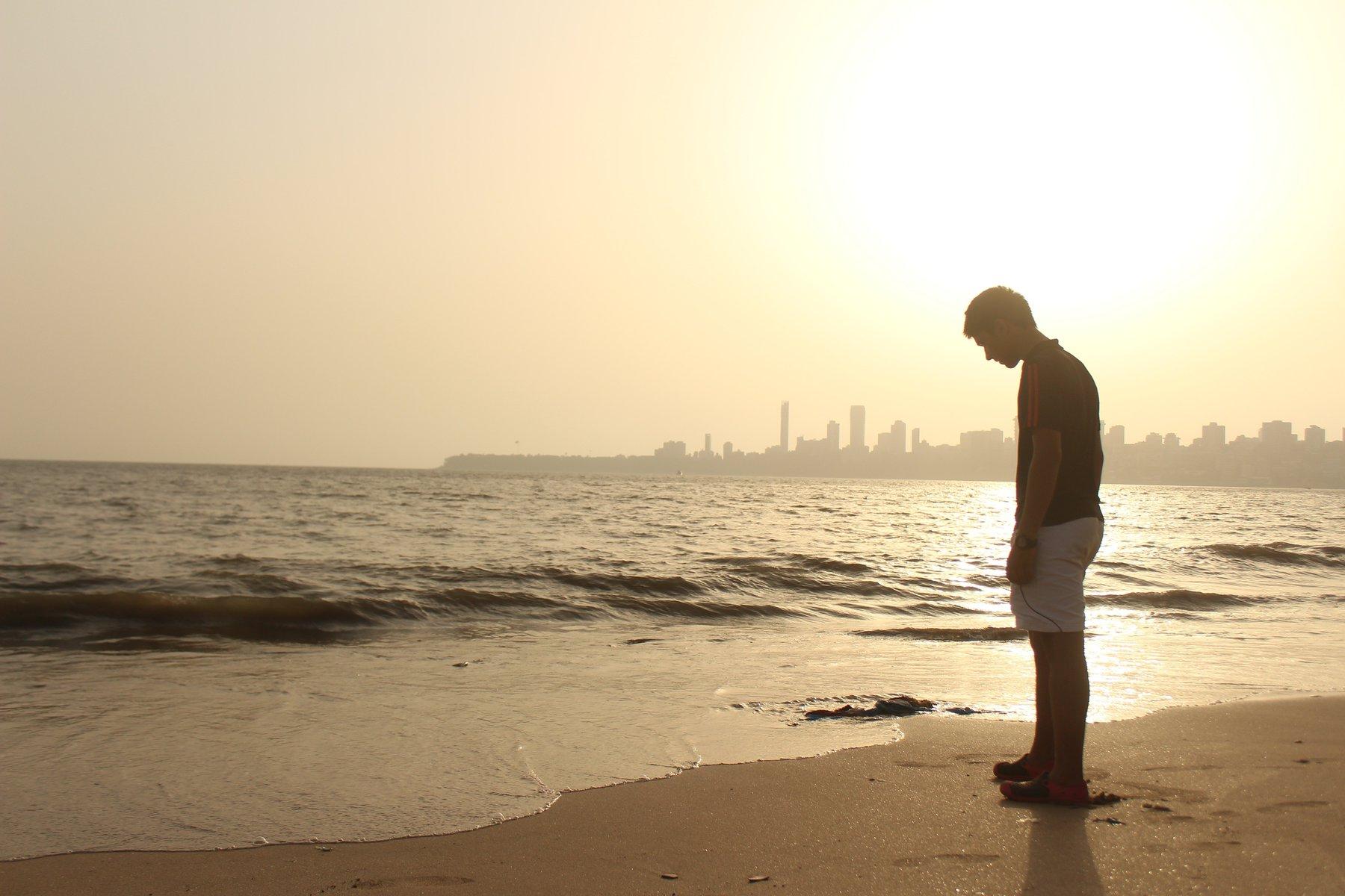 Homem cabisbaixo na praia