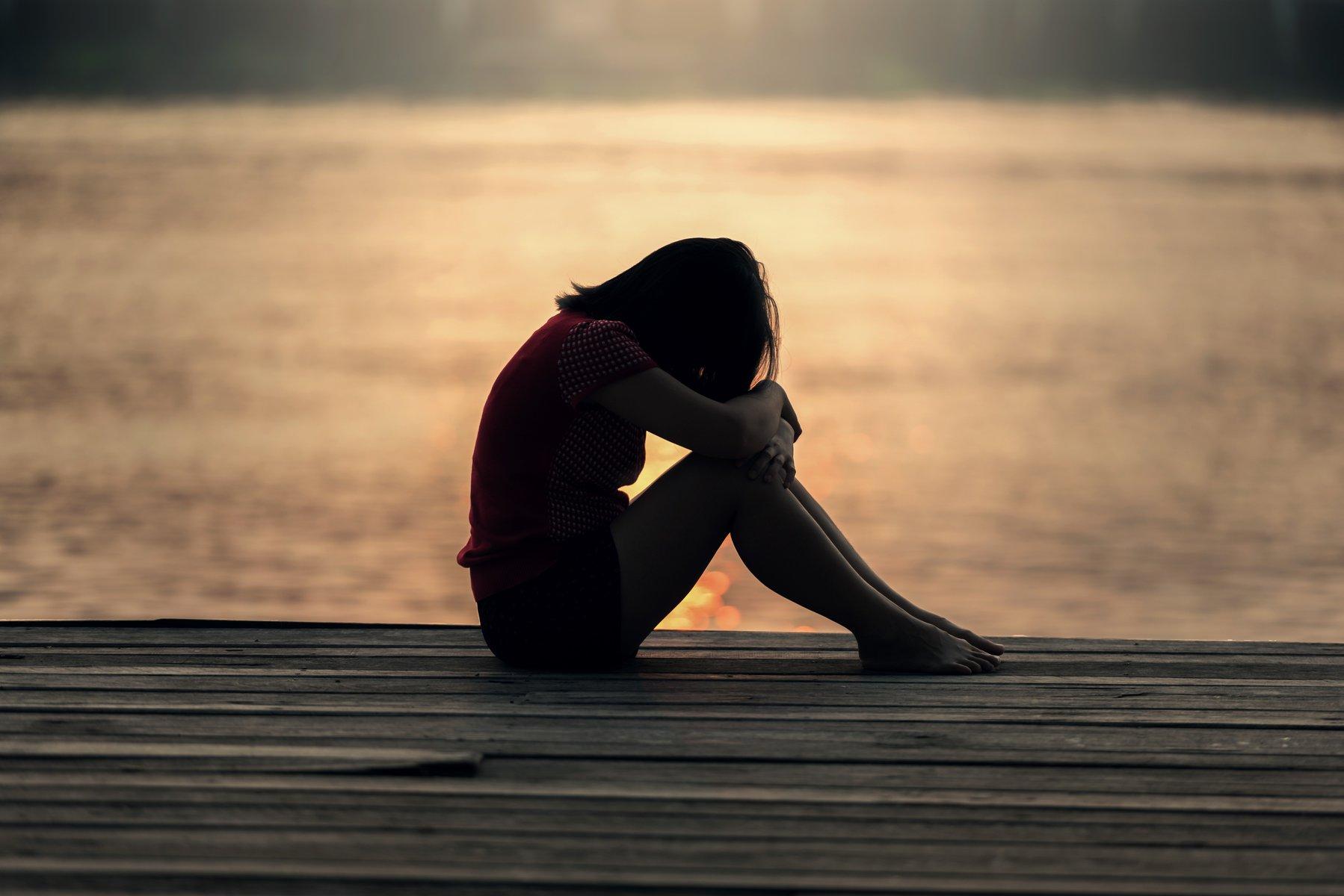 Mulher triste refletindo em frente ao mar