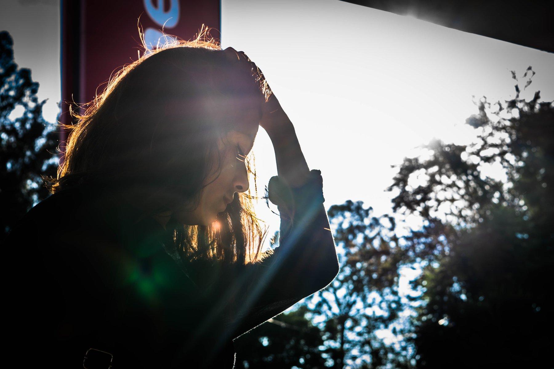 Mulher cabisbaixa com a mão a cabeça refletindo sob o sol ao fundo